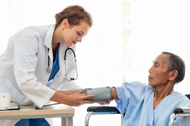 Médico profissional caucasiano de mulher verificar pressão arterial com paciente no quarto do hospital.