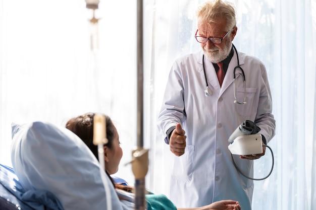 Médico profissional caucasiano sênior homem verificar pressão arterial com paciente mulher asiática na sala de hospital.