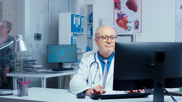 Médico profissional experiente, idoso, trabalhando em uma clínica movimentada, enquanto sua assistência está falando com o paciente no fundo e outras coisas de medicina médica estão passando. hospital clínico privado moderno