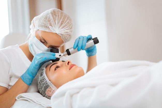 Médico profissional inteligente olhando para o dermatoscópio enquanto faz o exame de pele