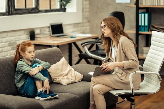 Médico profissional. mulher bonita e agradável olhando para sua jovem paciente enquanto quer ajudá-la