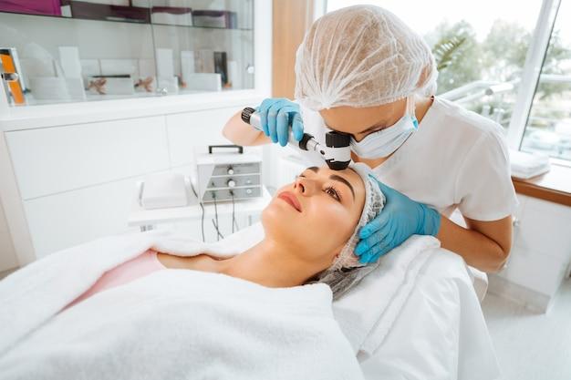 Médico profissional qualificado usando o dermatoscópio enquanto verifica a pele de seus pacientes