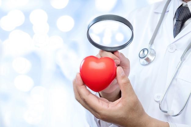 Médico profissional segurando uma lupa verifique um hospital vermelho da bola do coração
