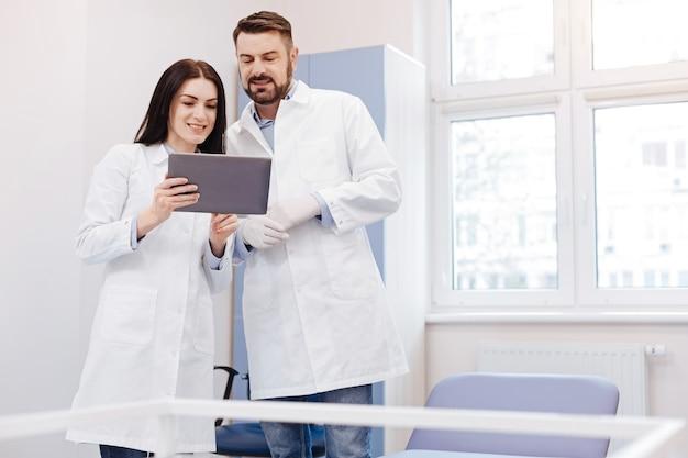 Médico profissional simpático segurando um tablet e olhando para a tela enquanto trabalha no escritório