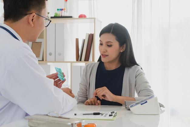 Médico profissional vestindo jaleco branco descreve como tomar remédio para paciente mulher.