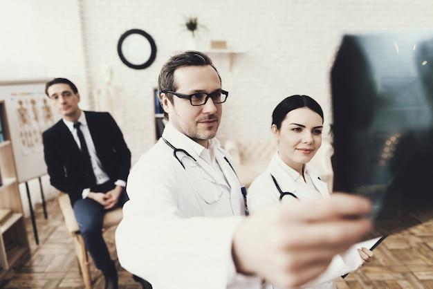 Médico qualificado com estetoscópio e enfermeira examinando o raio-x.