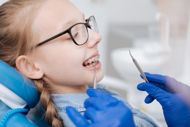 Médico qualificado e bem focado usando ferramentas especiais para verificar e manter dispositivos odontológicos especiais de seu pequeno paciente