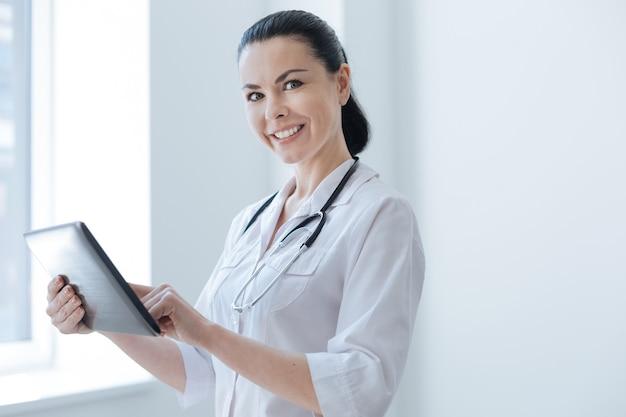 Médico qualificado sorridente positivo aproveitando o horário de trabalho na clínica enquanto está no armário e usando um dispositivo eletrônico