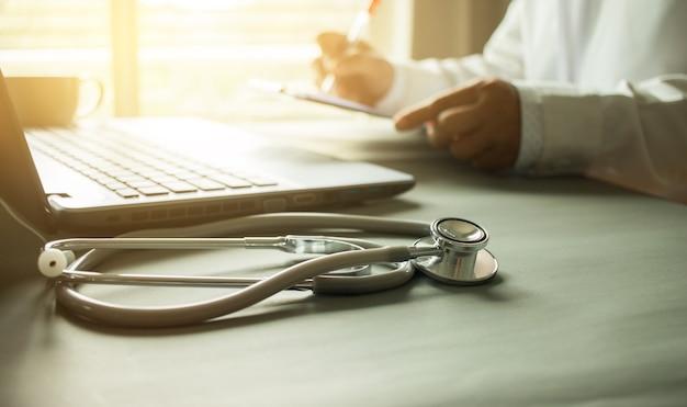 Médico que escreve uma receita no foco hospitalar no estetoscópio com prancheta e laptop na mesa, conceito médico e médico, cor vintage