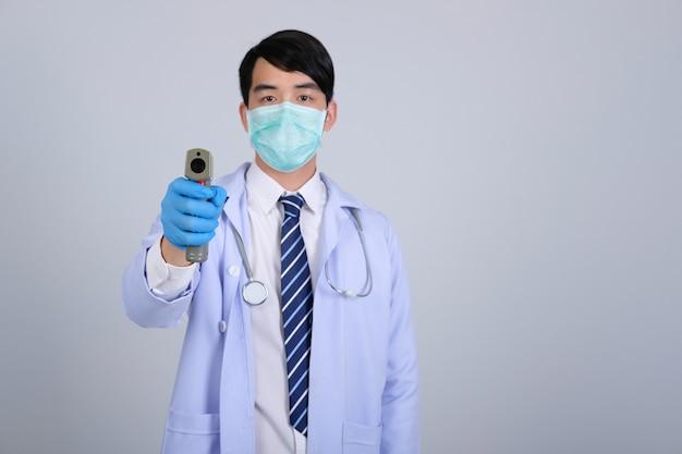 Médico que mede a temperatura corporal com pistola de termômetro infravermelho na testa