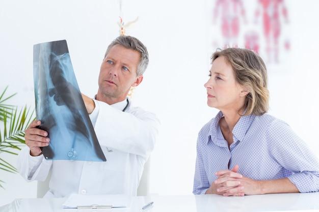 Médico que mostra o raio x ao paciente