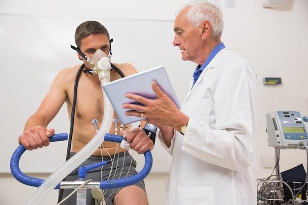 Médico que mostra o tablet pc para o homem fazendo teste de aptidão