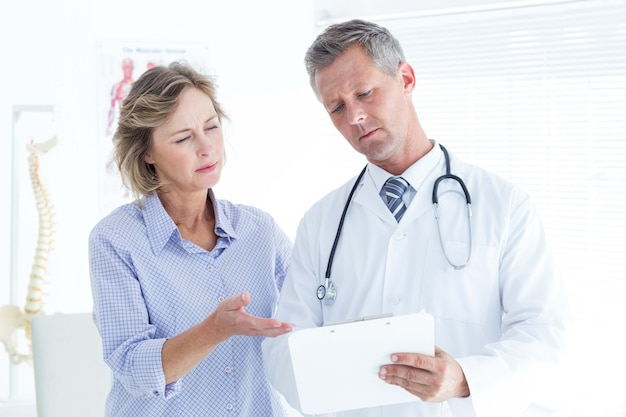 Médico que mostra suas anotações para o paciente