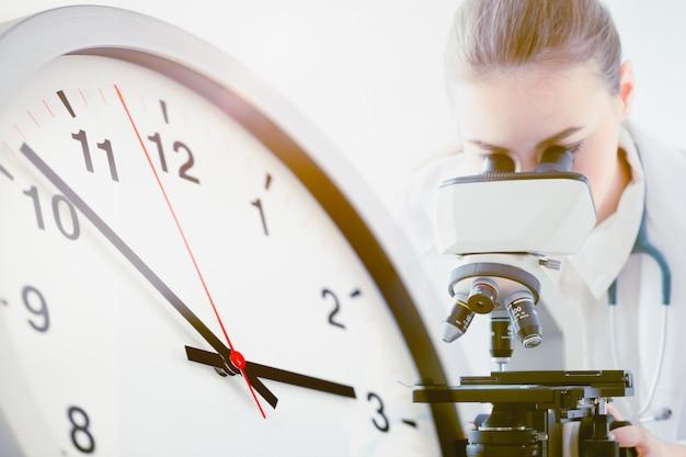 Médico que trabalha no laboratório com a face do relógio do times para cientistas pesquisando vacinas para competir com o tempo para combater o conceito covid-19