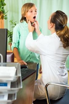 Médico que verifica a tireóide de adolescente
