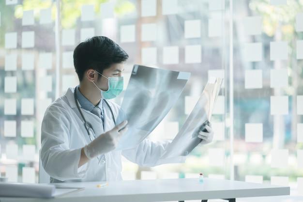 Médico que verifica examinando o filme de raio x do peito do paciente no hospital da ala. vírus corona covid-19 concept.