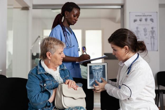 Médico radiologista analisando radiografia médica com mulher idosa doente