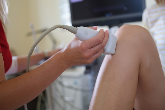 Médico realizando exame de ultrassom da articulação do joelho do paciente em diagnósticos clínicos de