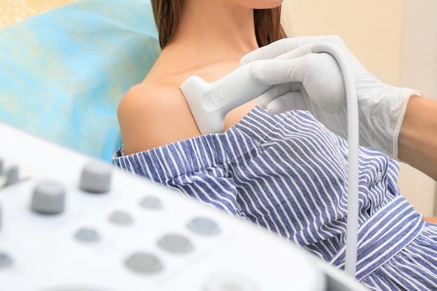 Médico realizando exame de ultrassom do ombro do paciente na clínica