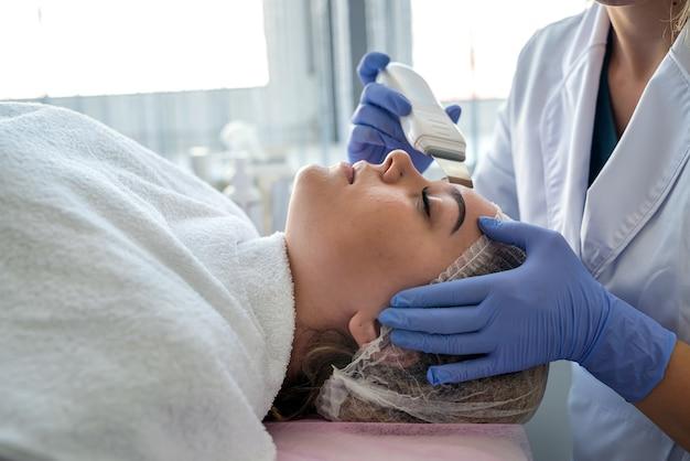 Médico realizando procedimento de limpeza ultrassônica de paciente facial em salão de beleza