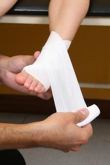 Médico realizar uma bandagem no tornozelo em uma menina