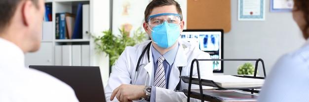 Médico recebe pacientes com máscara médica protetora