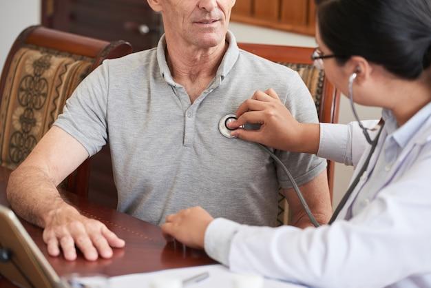Médico recortado, verificando o batimento cardíaco do paciente sênior