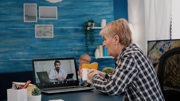 Médico remoto usando webcam prescrevendo remédios para mulher idosa doente sentada na sala de estar via estagiário ...