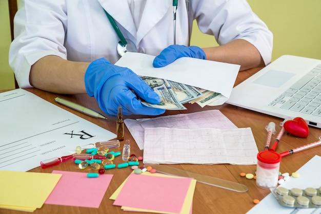 Médico retirando dólares do envelope no local de trabalho