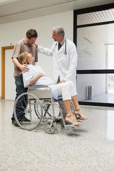 Médico rindo com mulher grávida em cadeira de rodas e parceiro