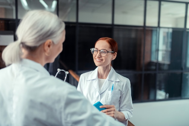 Médico ruivo. médica ruiva bonita de óculos sorrindo enquanto olha para sua colega de pé no corredor