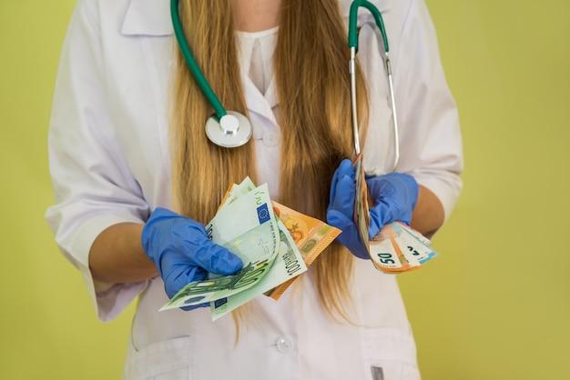 Médico segura o dinheiro do euro isolado no verde