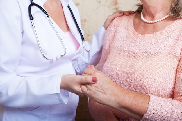 Médico segura uma senhora pela mão confortando