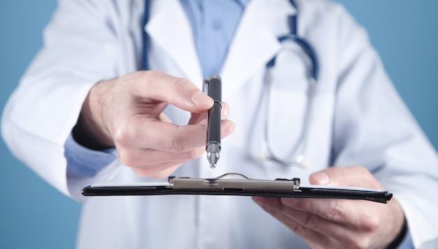 Médico segurando a caneta e a área de transferência.