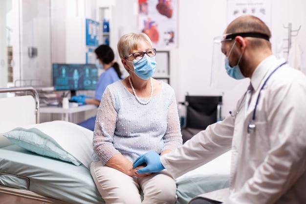 Médico segurando a mão de uma mulher sênior no hospital, dando compaixão em tempos de covid 19