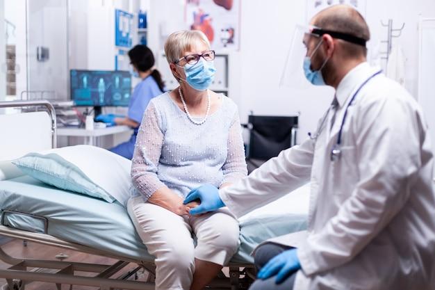Médico segurando a mão do paciente sênior dando incentivo durante a consulta em quarto de hospital
