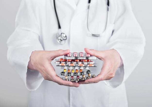 Médico segurando a pilha de diferentes pílulas, antibióticos e comprimidos de tratamento de vírus na parede cinza do hospital.