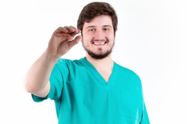 Médico segurando a pílula na parede branca