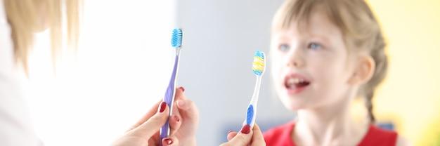 Médico segurando duas escovas de dente na frente da menina