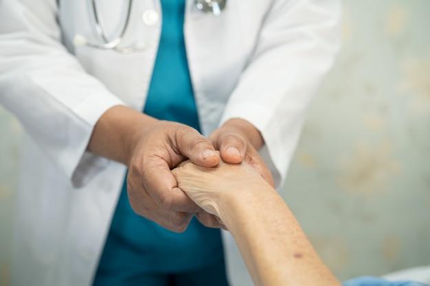 Médico segurando mãos comoventes paciente asiática sênior com amor