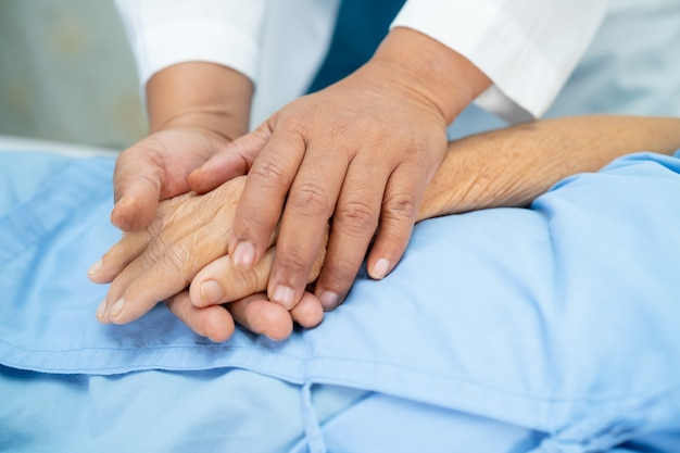 Médico segurando mãos comoventes paciente asiática sênior com carinho