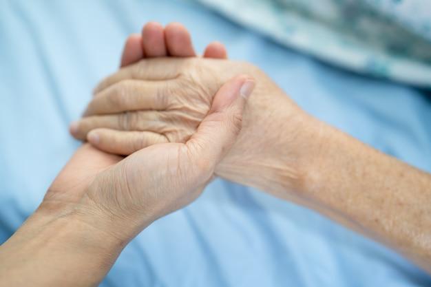 Médico segurando mãos comoventes, paciente idosa ou idosa asiática com amor