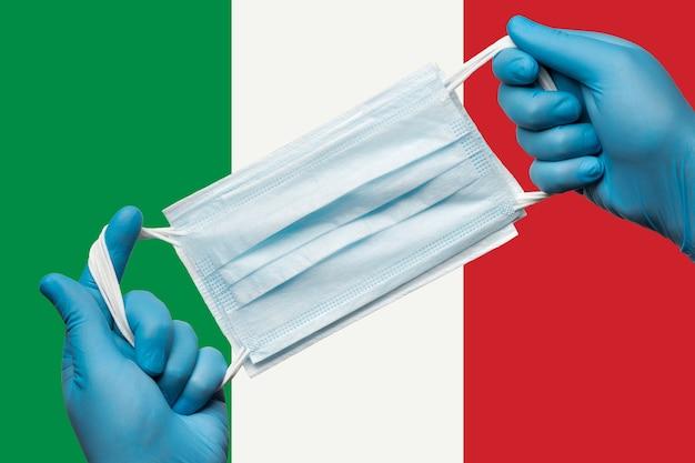 Médico segurando máscara respiratória nas mãos em luvas azuis na bandeira de fundo da itália ou italiano tricolor. quarentena de coronavírus de conceito e surto de pandemia. atadura médica para rosto humano.