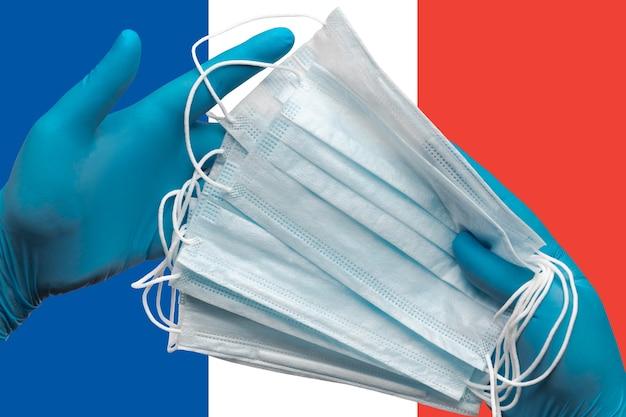 Médico segurando máscaras médicas nas mãos, luvas azuis no conceito de fundo da bandeira nacional da frança