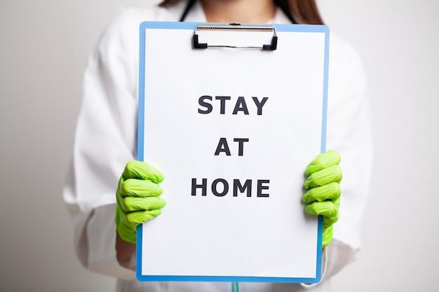 Médico segurando o formulário pedindo para ficar em casa durante a quarentena