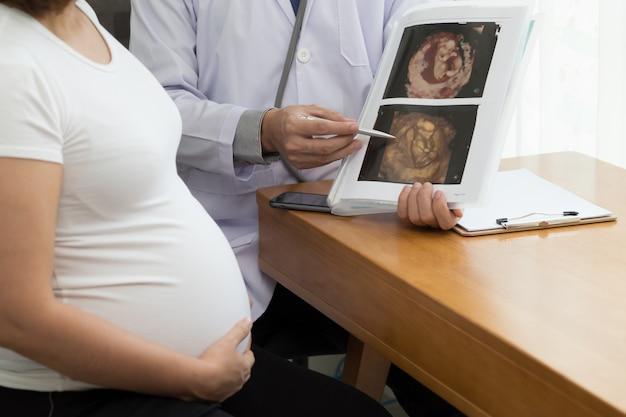 Médico segurando o resultado da imagem do ultra-som 4d e conversando com a mulher grávida. durante o conceito de gravidez