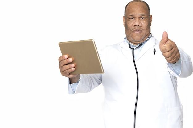 Médico segurando o tablet e apontando o polegar contra uma superfície branca