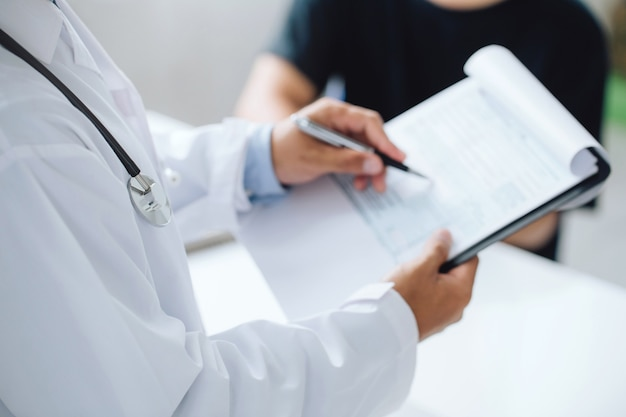 Médico segurando os resultados dos testes e consultando o paciente no consultório médico, conceito de profissionalismo de saúde em hospitais / clínicas