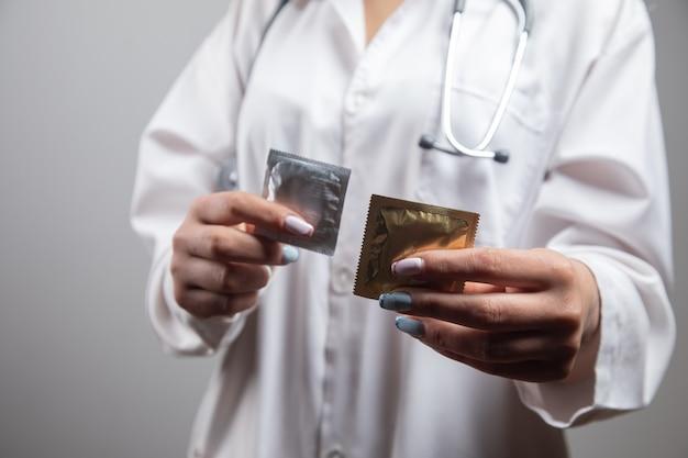 Médico segurando preservativos