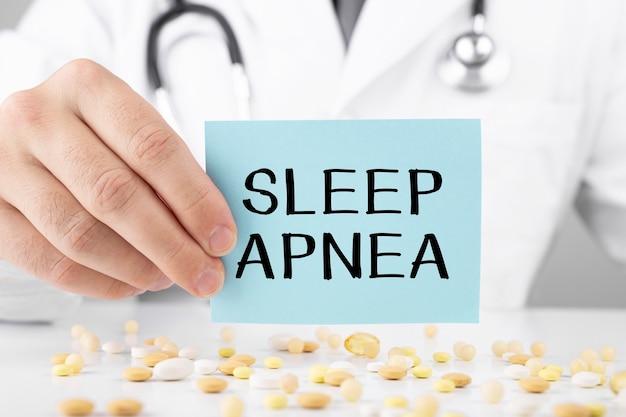 Médico segurando um cartão com o texto apnéia do sono, conceito médico